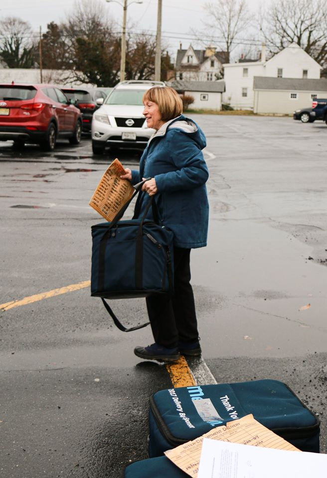 Joyce Bruno walking with a food delivery list and bag.