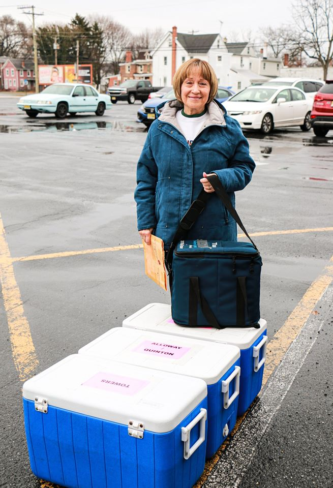 Joyce Bruno standing in parking lot with coolers and a food delivery bag.