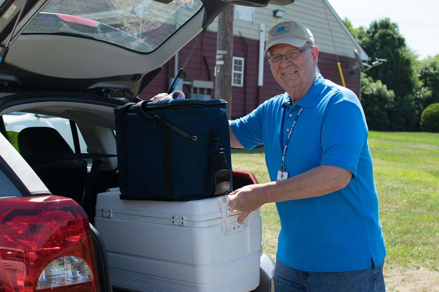 Ken Dennis loads a cooler and meal bag in the back of his vehicle.