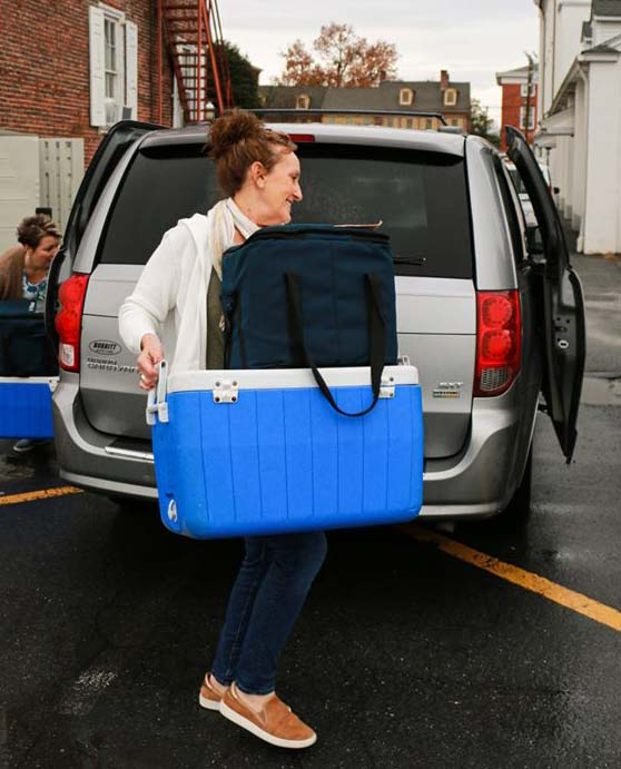 Nicki Burke moving large blue cooler behind a vehicle