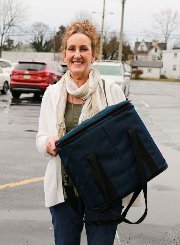 Nicki Burke smiling and holding a good delivery bag.