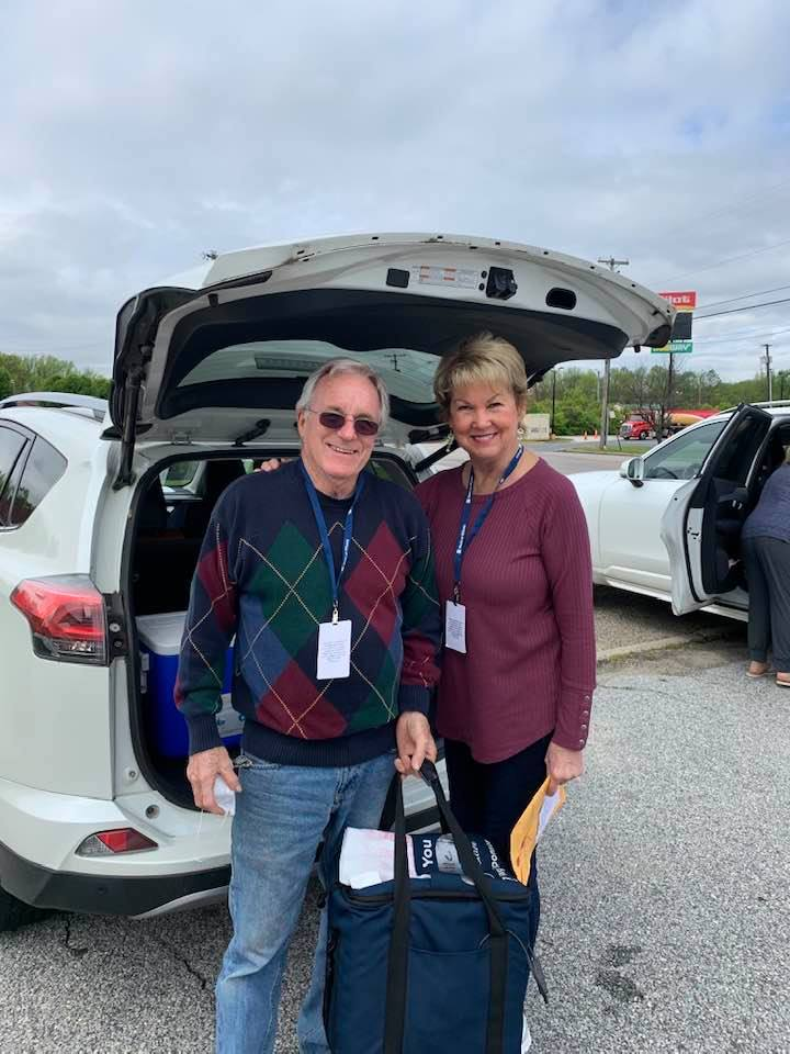Craig & Gaynel Schneeman holding bag infront of opened trunk