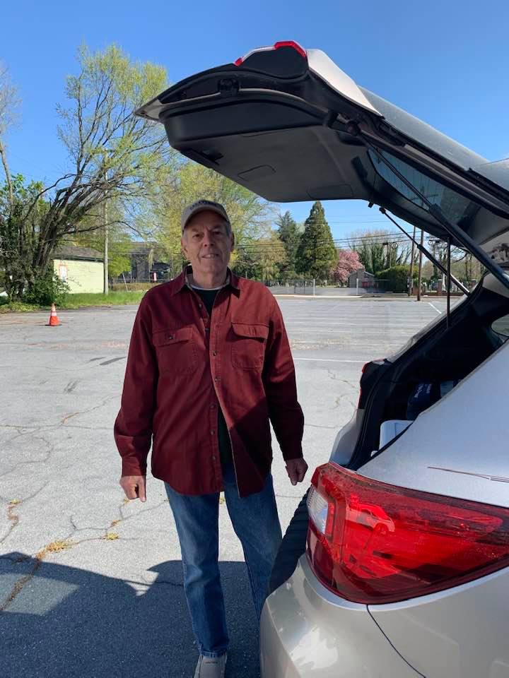 George Marshall standing infront of SUV's open trunk