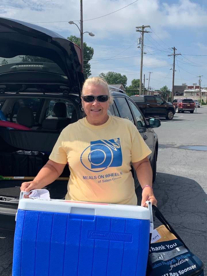 Cheryl Schenkel carrying large blue cooler