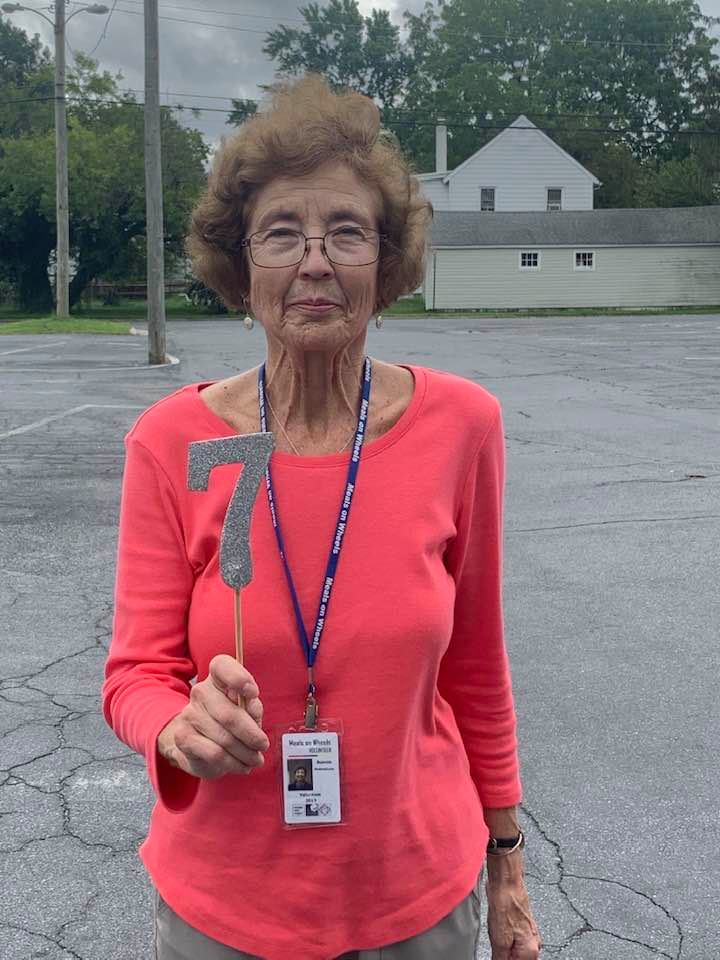 Bonnie Holstrum holding up cut-out of number 7