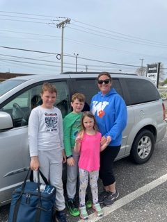 Mother with children standing in front of a van